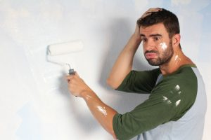Stressed out male painting his home